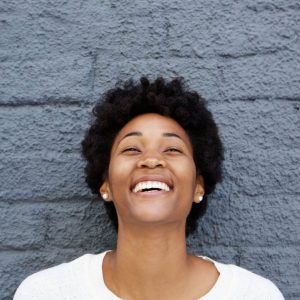 Image of a happy patient who has learned about the benefits of a dental crown.