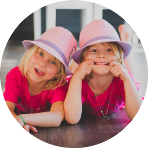 Image of two happy little girls who are curious to learn about the tooth fairy and baby teeth.